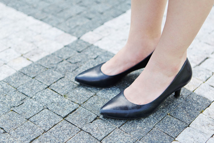 Low Section Of Woman Wearing Heels While Standing On Footpath