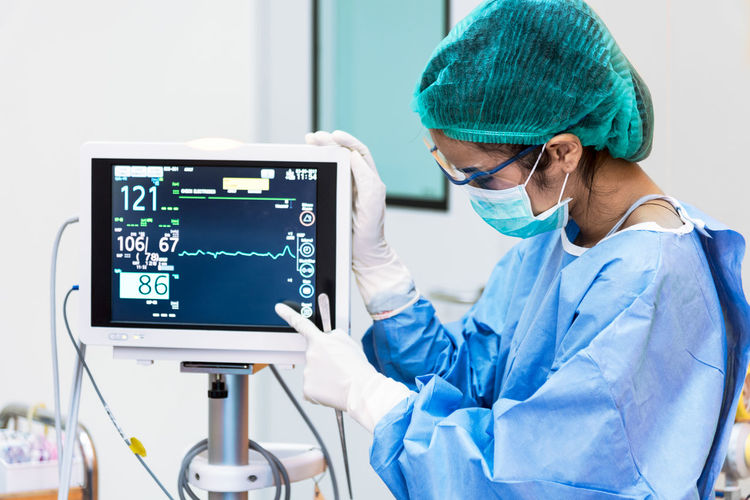 Surgeon checking monitoring equipment in operating room at hospital