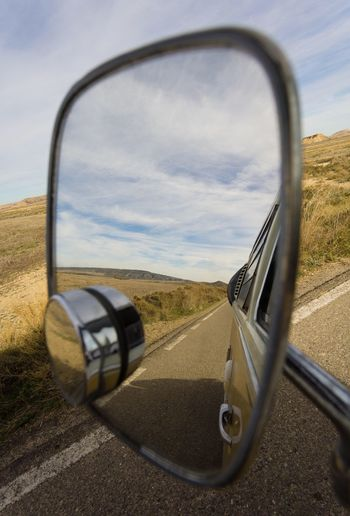 Close-Up Of Side-View Mirror Against Sky