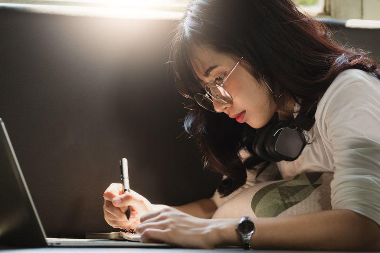 Young woman using mobile phone while sitting in pen