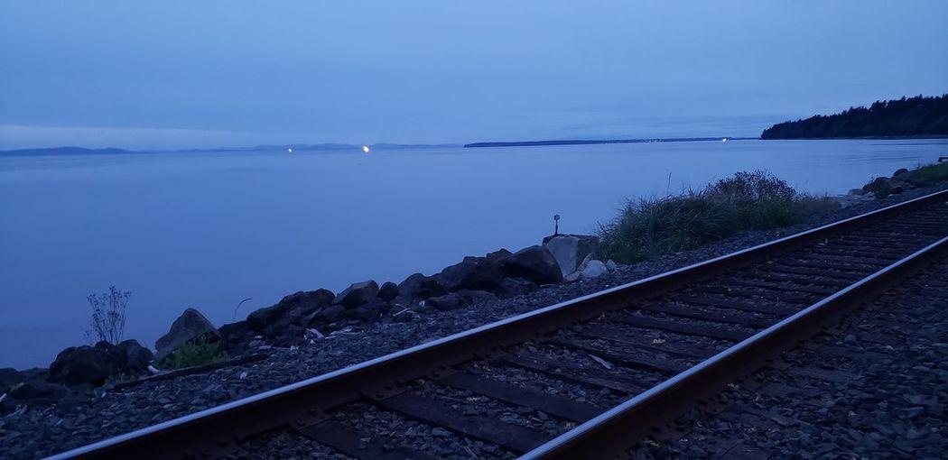 Railroad tracks by sea against sky