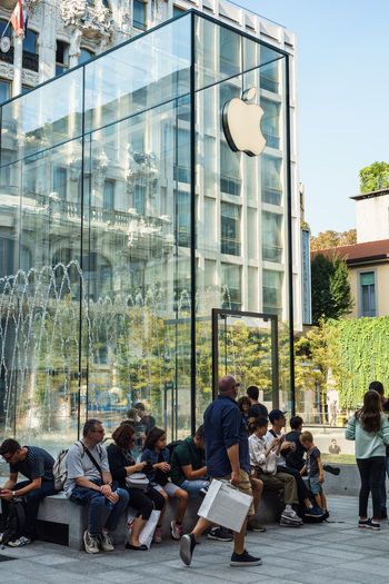 Apple Apple Store Adult Architecture Building Exterior Built Structure City Crowd Day Glass - Material Group Of People Lifestyles Men Office Building Exterior Outdoors People Real People Reflection Sitting Street Window Women