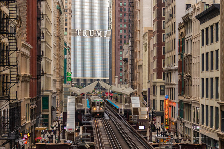 """Love him or hate him; Trump is certainly impossible to avoid. This shot is looking down over the Chicago, """"L"""" which is the second-oldest rapid transit system in the Americas dating back to 1892. The """"L"""" is derived from the elevated nature of the system above the streets which make it such a distinctive part of the city. Taken with a 150mm focal length to get some perspective compression. Built Structure Architecture Building Exterior Track City Rail Transportation Railroad Track Transportation Building Mode Of Transportation Public Transportation Day City Life High Angle View on the move Travel Train Street Car Office Building Exterior Outdoors Skyscraper Trump Chicago Architecture Chicago, L"""
