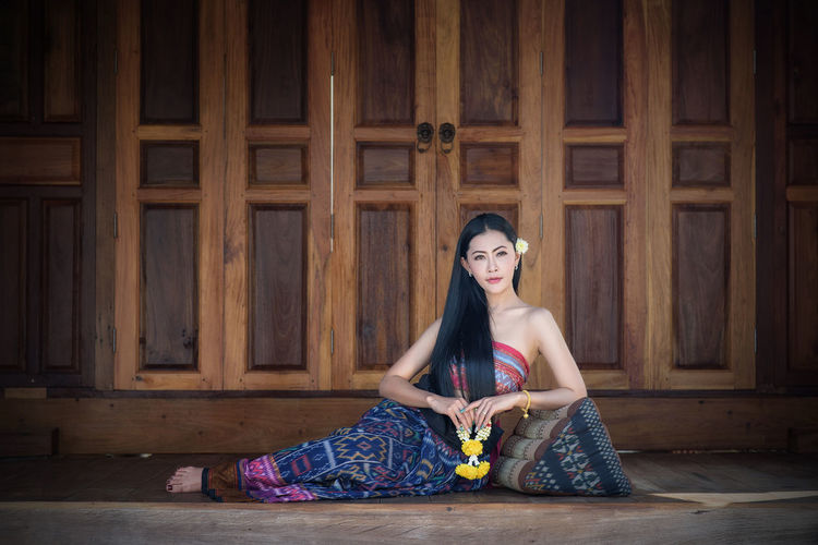 Young woman relaxing against closed wooden door