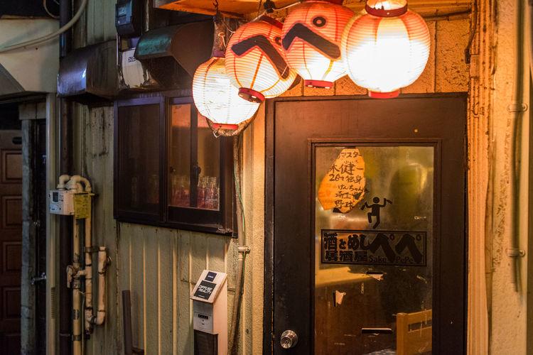 Illuminated lanterns hanging on building