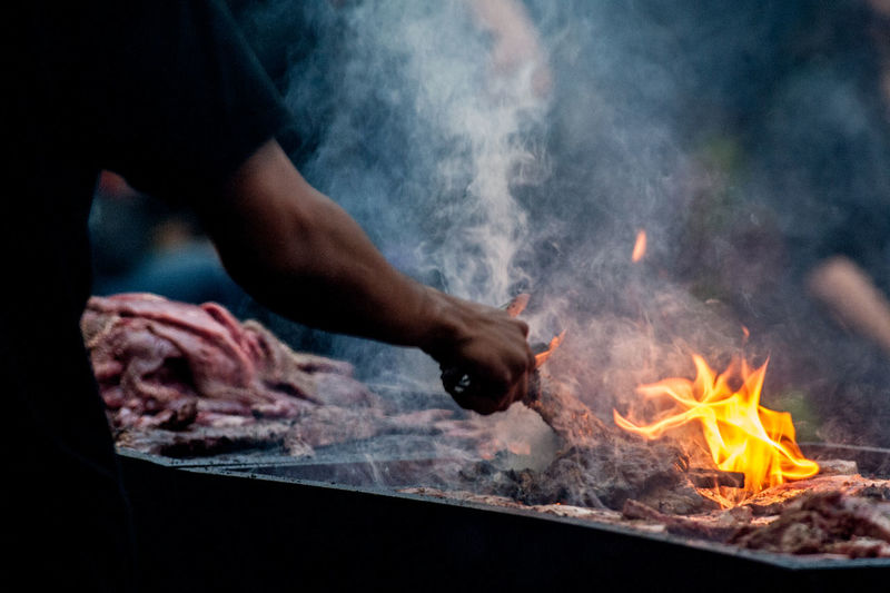 Midsection hand of man holding serving tongs by burning barbecue