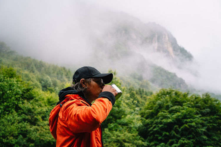 Man in orange jacket drinking from cup against foggy mountains