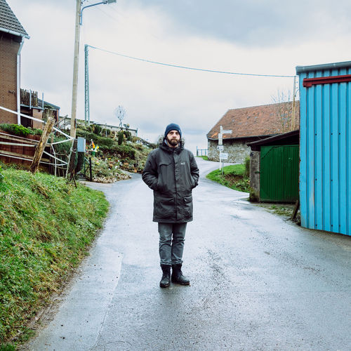 Portrait of man standing on road in village