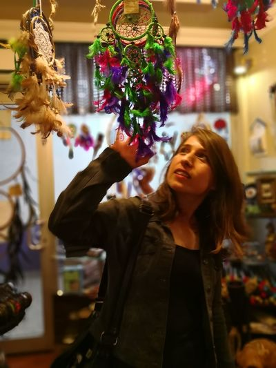 Woman Touching Dreamcatchers For Sale In Store