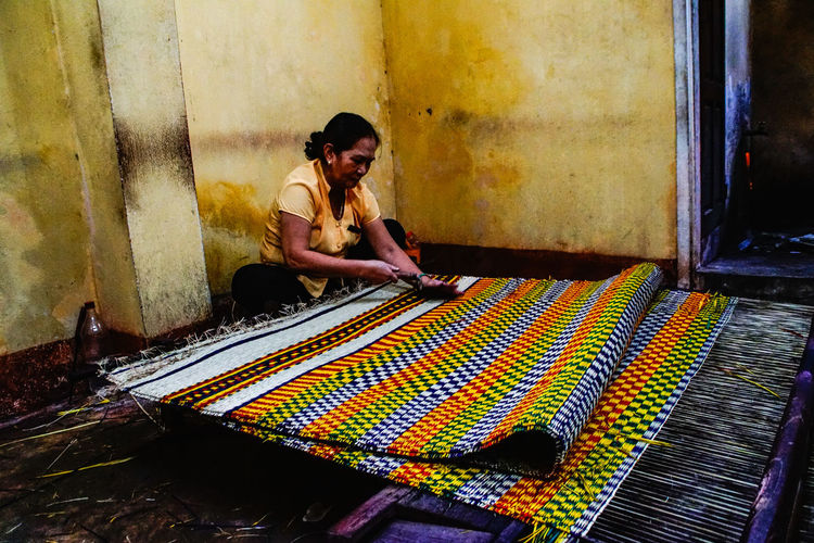 Textile industry in Vietnam where a woman is weaving a carpet Vietnamphotography Vietnam Colorful Cultural Makealiving Yellow Working Working Woman Weaving Third World Country Multi Colored Sitting ArtWork Art Fabric Handmade Textile Representation Art And Craft Carpet Focus On The Story