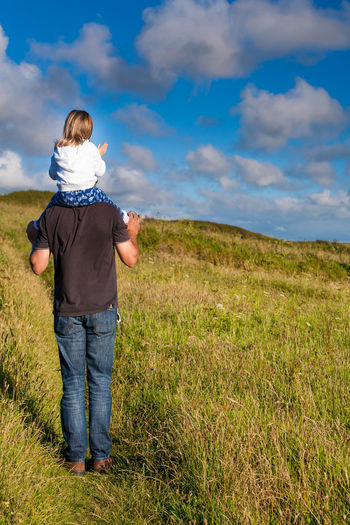 Father Carrying Daughter On Shoulder While Walking On Grassy Field Against Sky