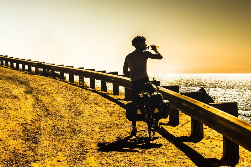 Man on bicycle standing by railing against sky during sunset
