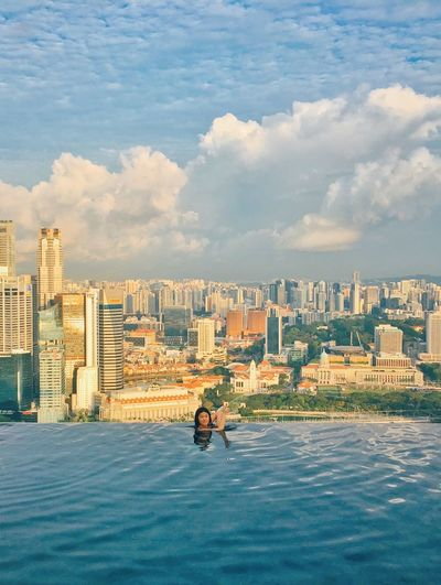 Woman swimming in infinity pool against cityscape and cloudy sky