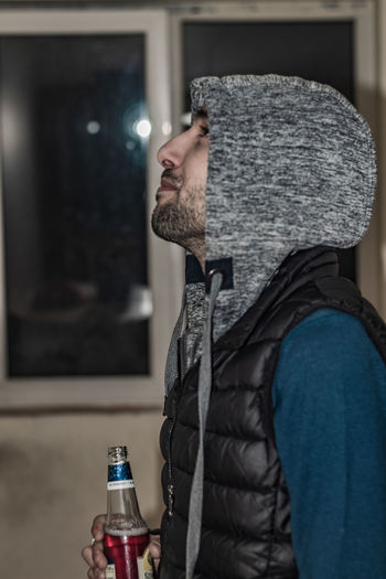 Side view of young man in hood drinking beer indoors