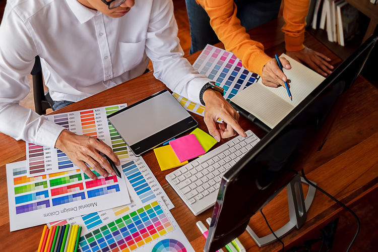 Midsection of colleagues analyzing color swatch in office