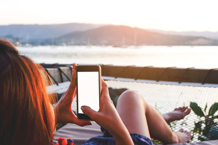 Woman using mobile phone while sitting on lounge chair