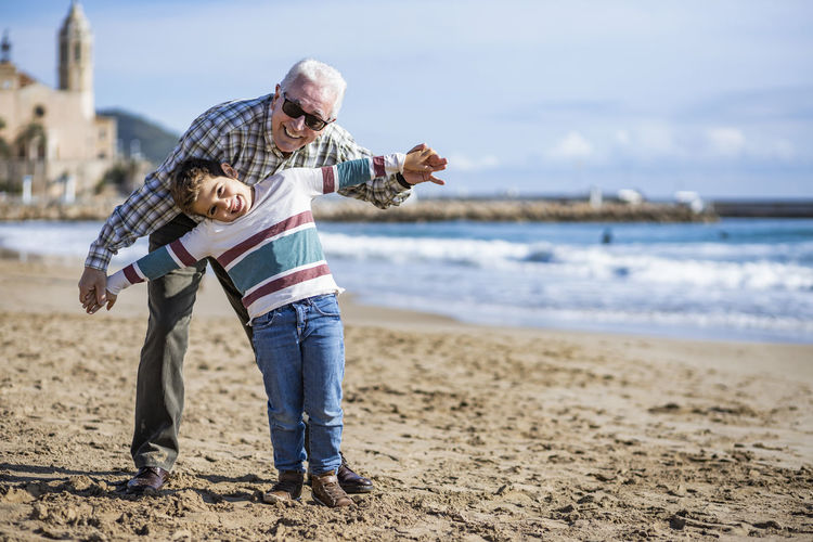 Portrait of happy senior man playing with grandson at beach