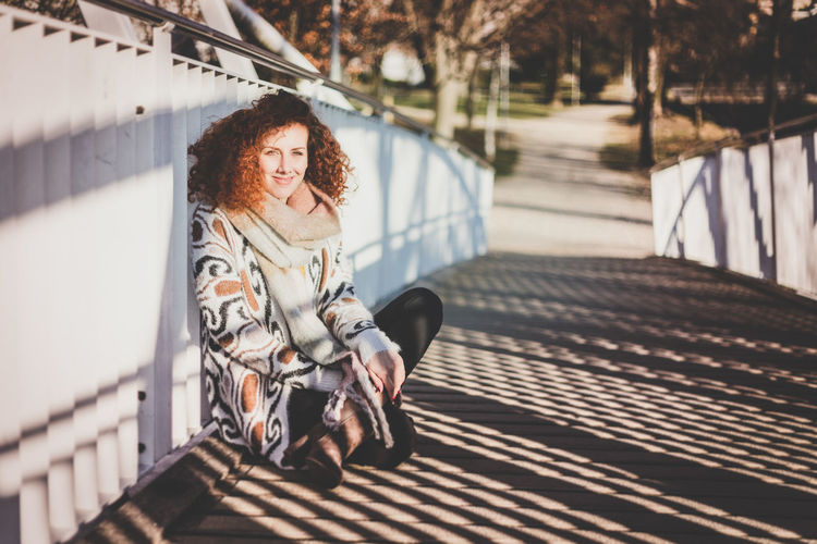 Portrait Of Smiling Woman Sitting On Footbridge