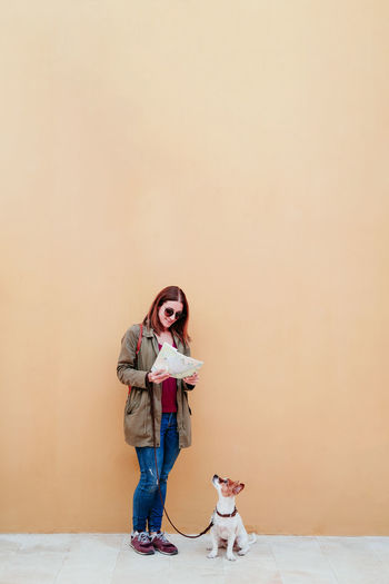 Woman with dog standing against wall