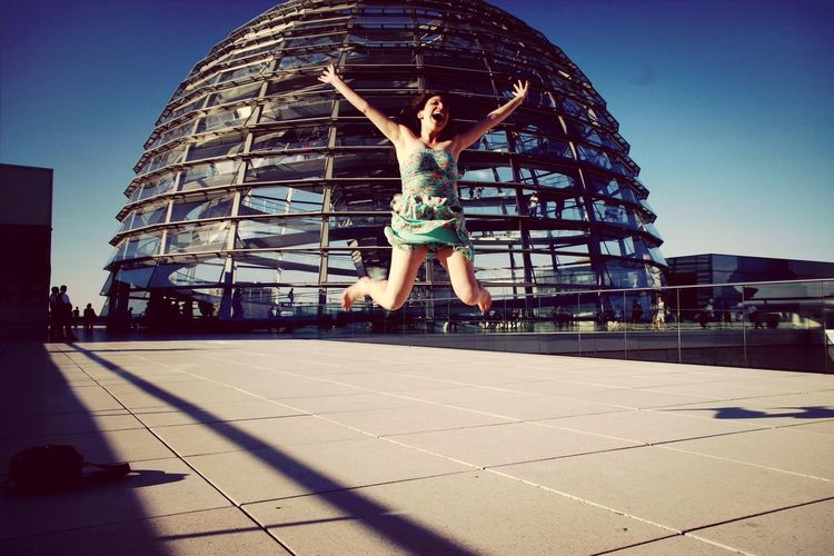 Woman jumping in front of reichstag dome