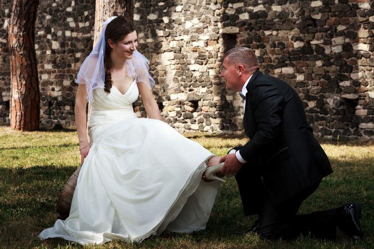 Groom putting high heels in bride foot on land