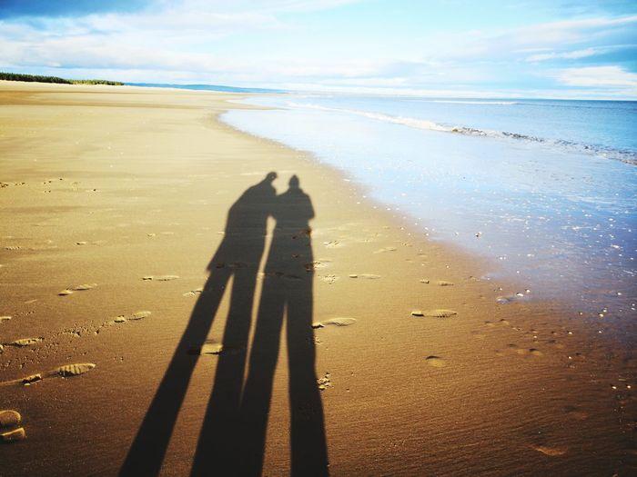 Shadow of people on beach against sky