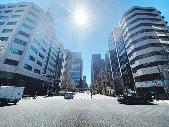 Modern buildings against sky on sunny day