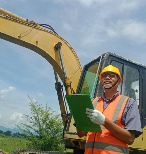 Man working with yellow umbrella against sky