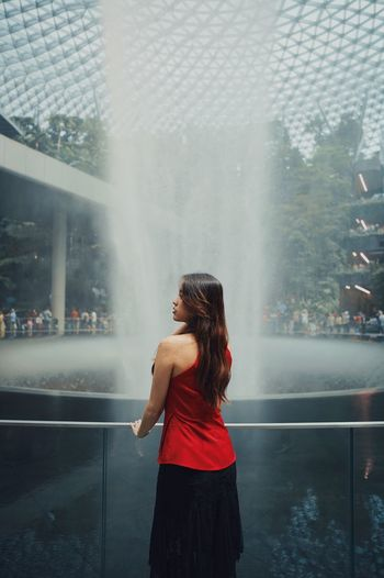 Rear view of woman standing by fountain outdoors