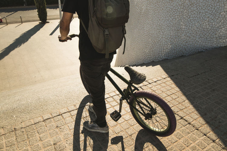Low section of man with bicycle on street