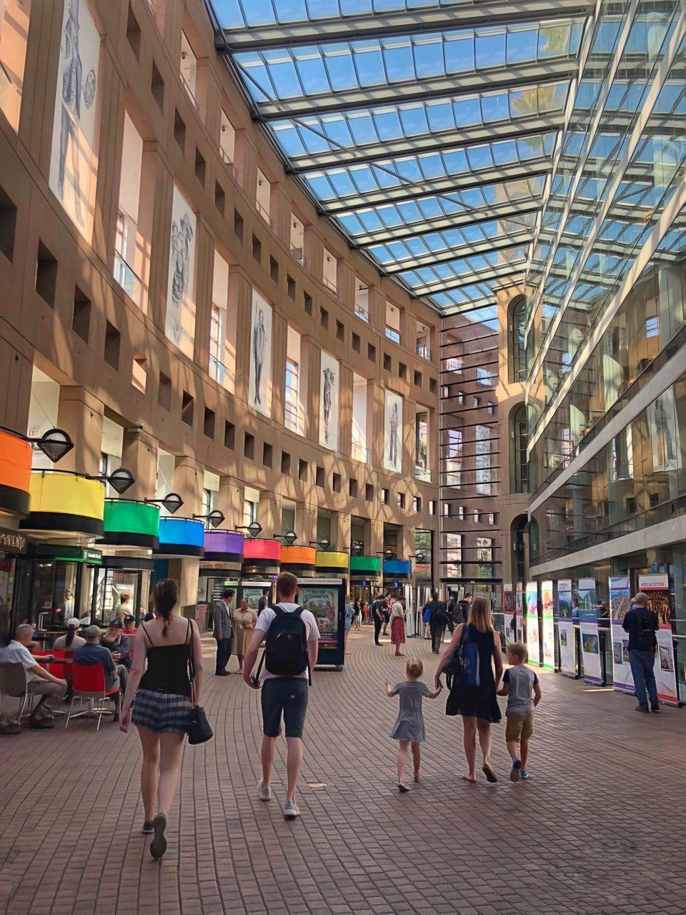 GROUP OF PEOPLE WALKING IN MODERN BUILDING