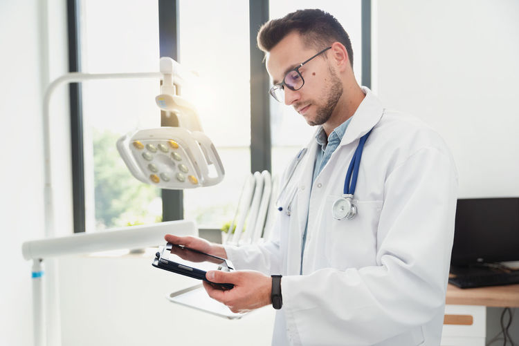 Doctor looking at digital tablet while standing at medical clinic