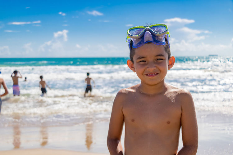 Portrait of smiling shirtless boy with swimming goggles standing at beach during summer