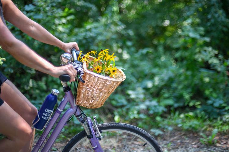 Man riding bicycle in basket