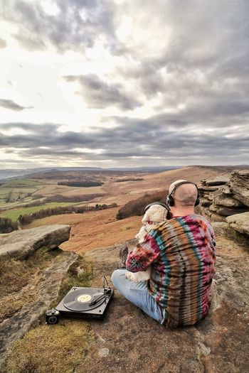 Man with dog listening music on land against cloudy sky