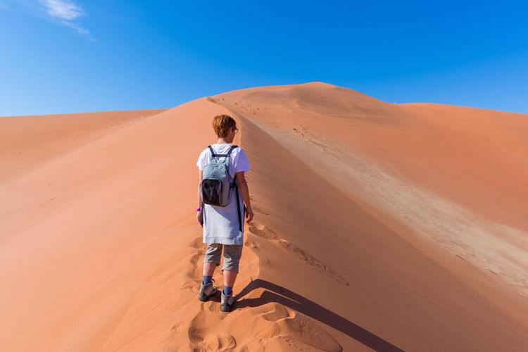 Rear View Of Female Tourist Standing At Namib Desert In Naukluft National Park During Sunny Day