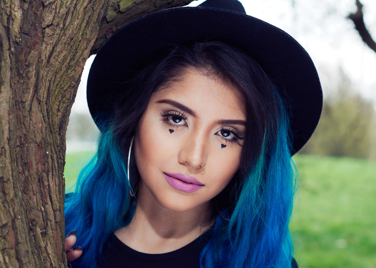 Portrait Of Smiling Woman With Blue Dyed Hair Standing By Tree Trunk