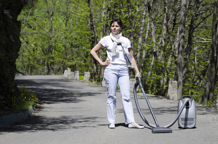 Proud woman on a street with her vacuum cleaner Adults Only Cleaning Color Concept Day Elegant Forest Hand On Hip Humor Looking At Camera Nature One Person One Woman Only Outdoors People Protection Proud Road Scarf Standing Up Street Sunny Tree Area Vacuum Cleaner Woman