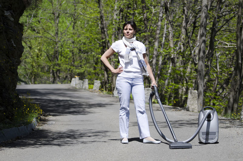 Full length of woman with vacuum cleaner standing on road amidst trees