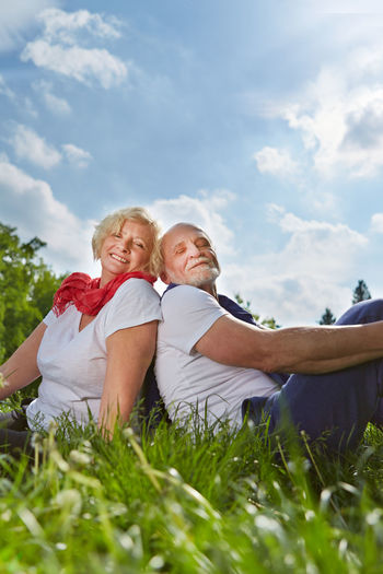 Portrait Of Senior Couple Sitting On Field