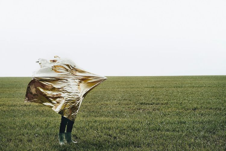 Person covering with foil standing on field against clear sky