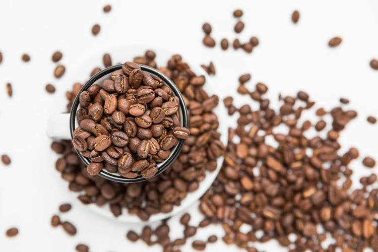 Top View of Coffee beans in a White Coffee cups on White Background Roasted Coffee Bean Food And Drink Coffee - Drink Brown Coffee Freshness Food Indoors  Drink Large Group Of Objects High Angle View Close-up Cup Table Roasted Refreshment Still Life Mug No People Coffee Cup Caffeine Crockery
