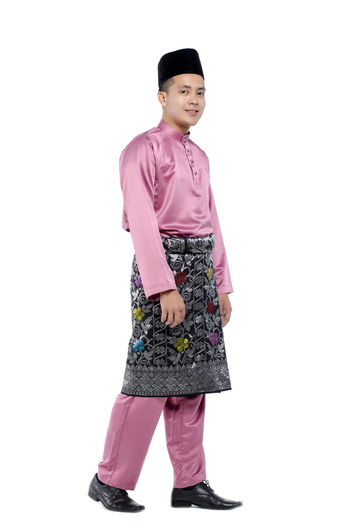 Portrait of young and handsome asian man with traditional clothing during hari raya over white background Studio Shot White Background One Person Full Length Child Childhood Indoors  Standing Girls Clothing Females Pink Color Front View Cut Out Copy Space Lifestyles Looking At Camera Innocence Pre-adolescent Child Purple