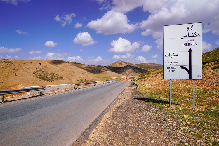 En-route on our way in Azrou. Sign Communication Road Transportation Sky Western Script Direction Road Sign Text Cloud - Sky Day Information Nature Mountain Guidance No People The Way Forward Symbol Script Information Sign Outdoors Arid Climate Climate
