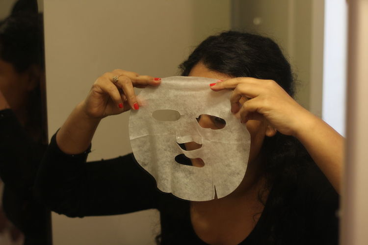 Woman using facial mask at home