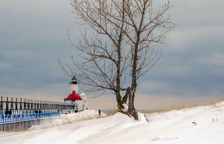 winter light house in St Joseph Michigan , on the shores of Lake Michigan USA Weather Winter Snow Cold Temperature White Background Great Lakes Michigan USA Landmark St Joseph Michigan Light House Safety Building Exterior Architecture Horizontal Dusk Seasonal Landscape Snowy Days... Travel Pier Structure Tree Nature Landscape