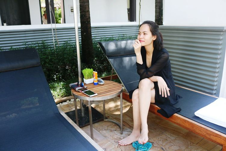 Young woman looking away while sitting on lounge chair
