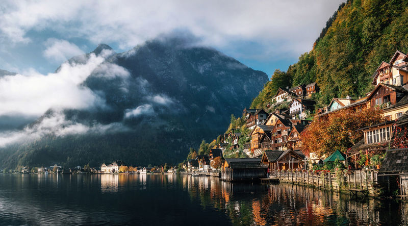 Scenic view of famous Hallstatt lakeside town reflecting in Hallstattersee lake in the Austrian Alps in morning light in autumn with clouds, Salzkammergut region, Austria Alpine Austria Landscape_Collection Alps Austria Built Structure Cloud - Sky Hallstatt Lake Landscape_photography Mountain Mountain Range Outdoors Scenics Sky Tranquility Tree Water Waterfront