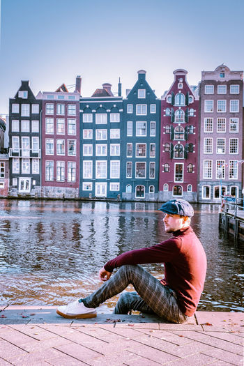 Side view of man sitting against buildings in city