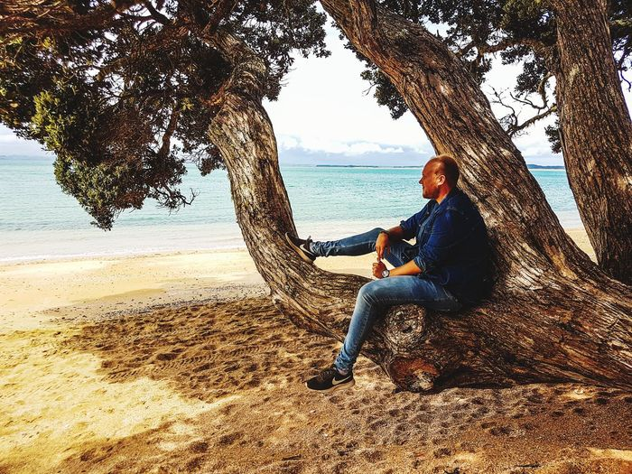Woman sitting on tree trunk by sea against sky